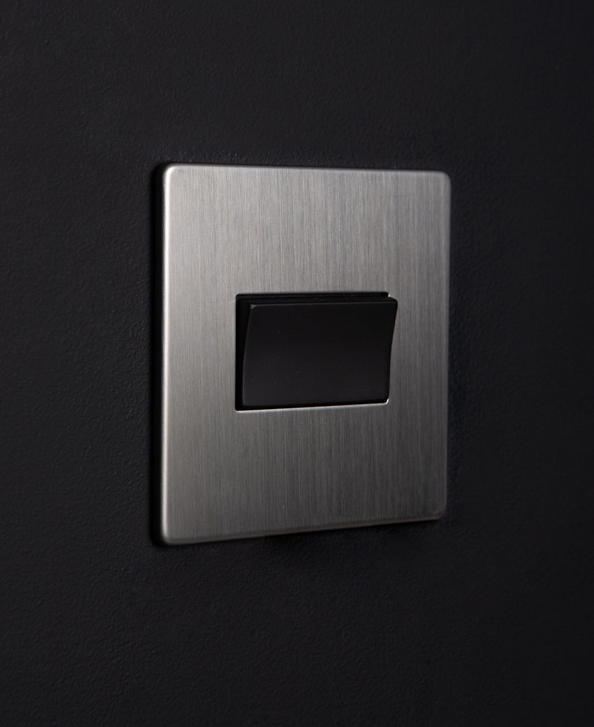silver and black fan switch against black background