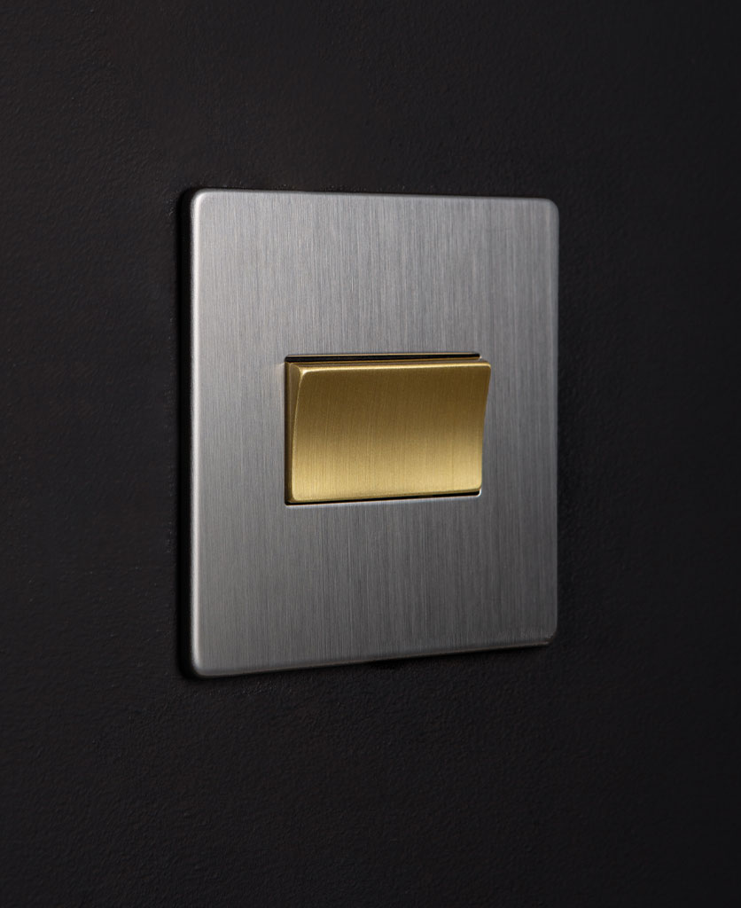 silver and gold fan switch against black background