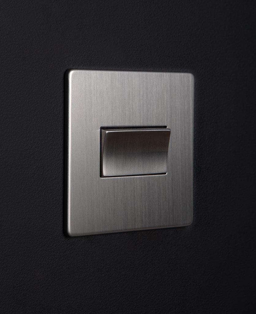 silver fan switch against black background