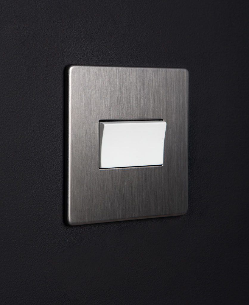 silver fan switch with white detail against black background