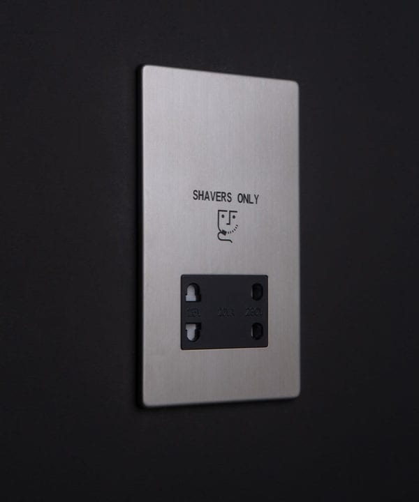silver and black shaver socket against black wall