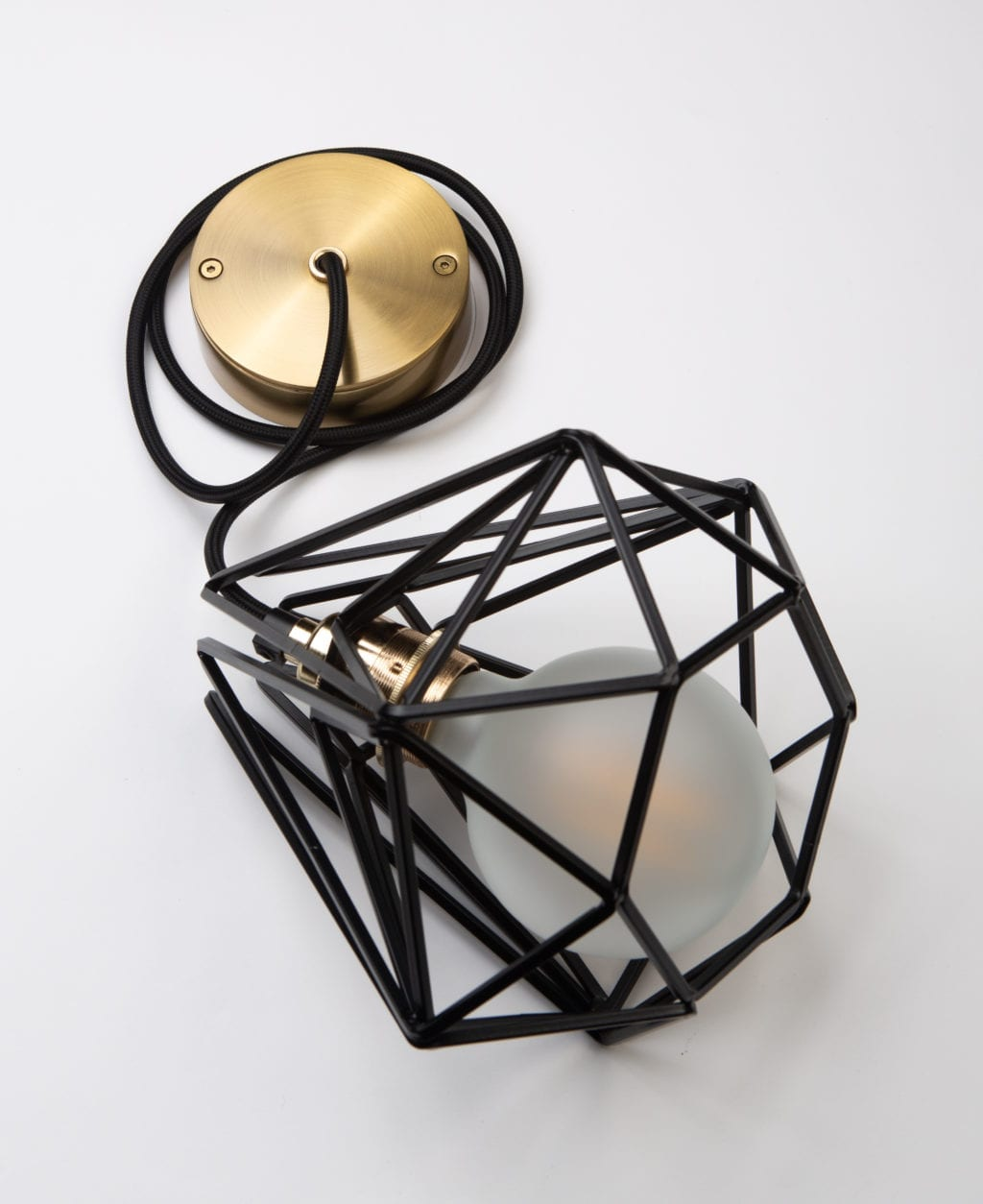 small black cage pendant light with frosted light bulb, black fabric cable, gold bulb holder and gold ceiling rose against white background