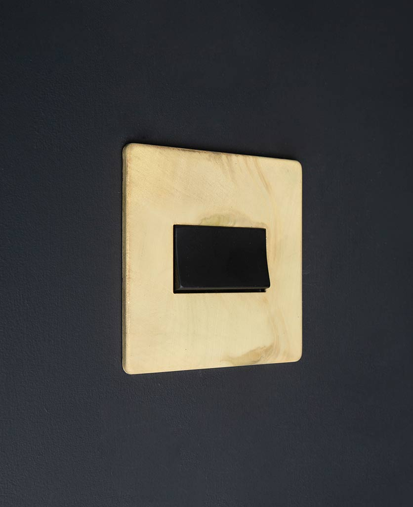 smoked gold and black fan switch against black background