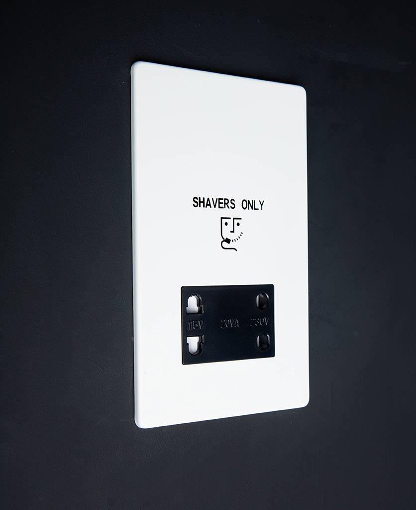 white and black shaver socket against black background