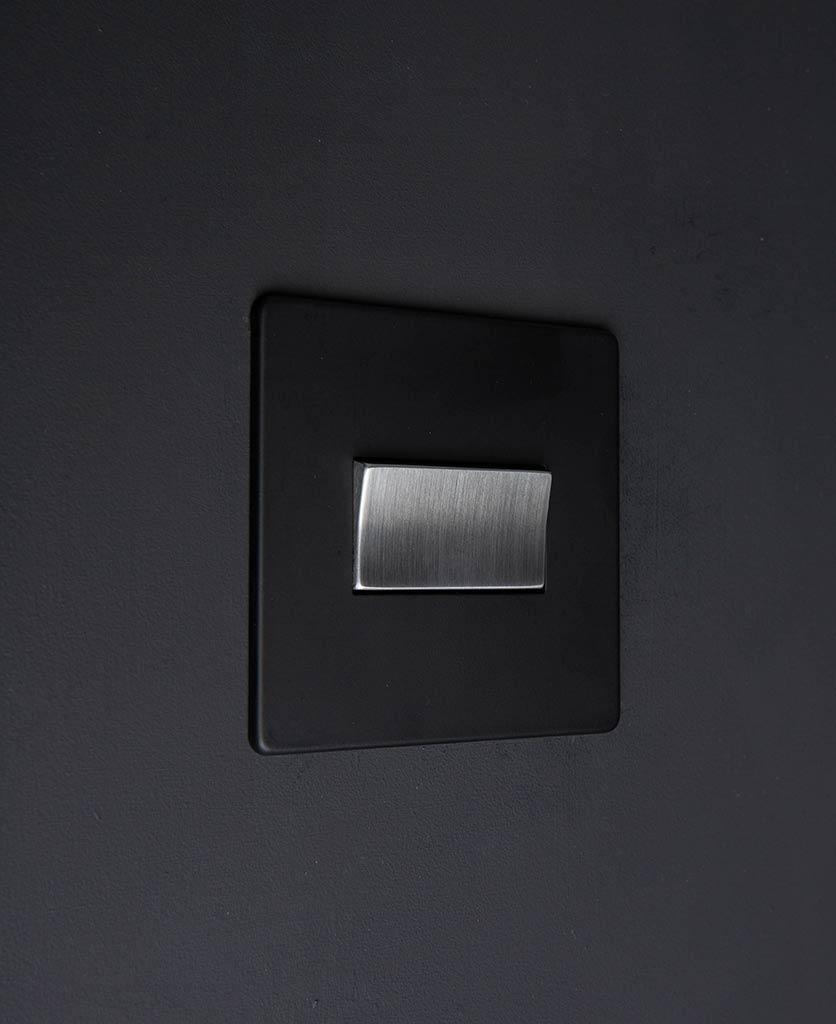 black & silver triple pole fan switch on black wall