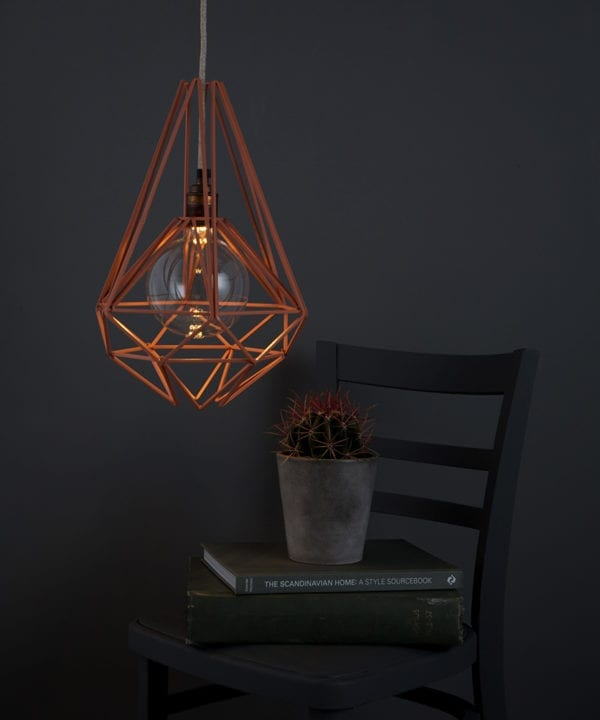 pink chai cage light shade suspended from grey jumper cable against grey background