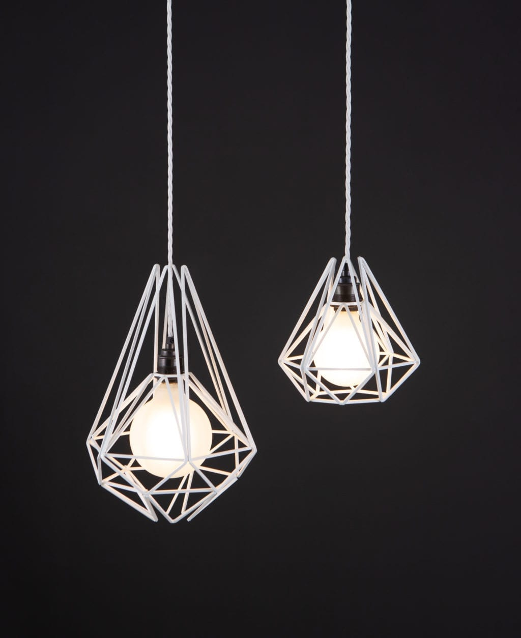 white metal pendant light with frosted bulb suspended from white twisted fabric cable against black background