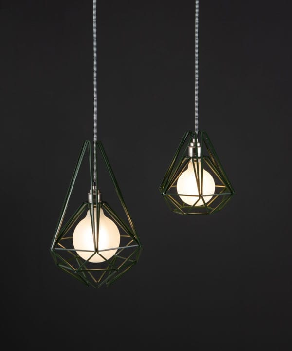 green metal cage light with frosted bulb suspended from black and white fabric cable against black background