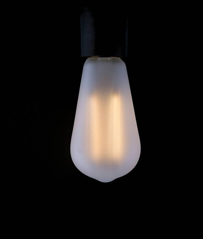 frosted pear squirrel cage filament bulb with a warm glow against a black background