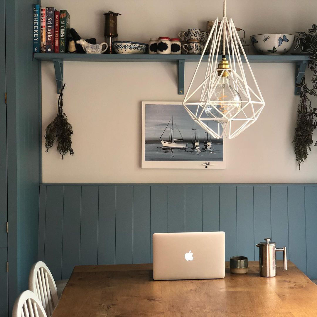 Oolong cage pendant light suspended above a dining table in a bglue and white interior