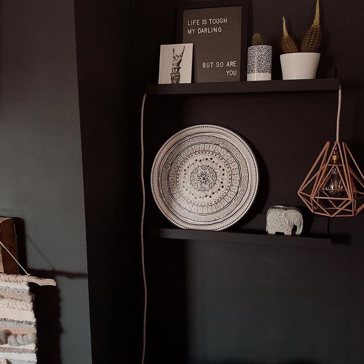 pink chai table lamp on a black bookcase with monochrome ornaments