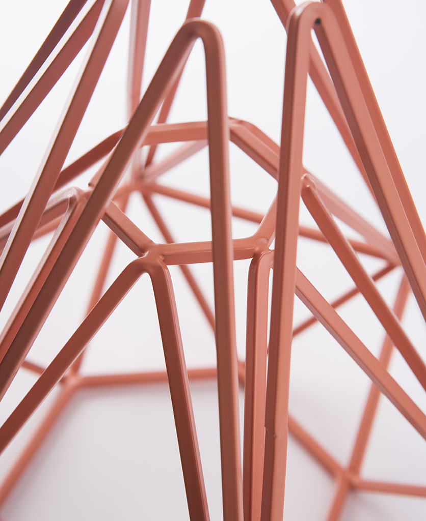 pink chai cage table lamp close up against white background