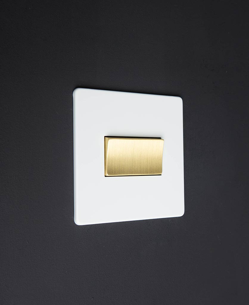 white and gold fan switch against black background