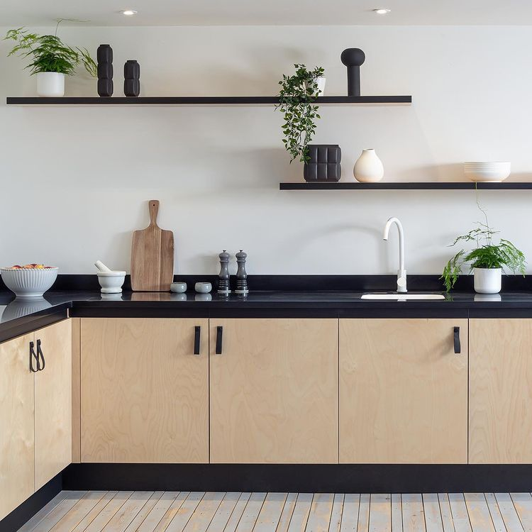 Magni handles on wooden cupboards ina white and black kitchen