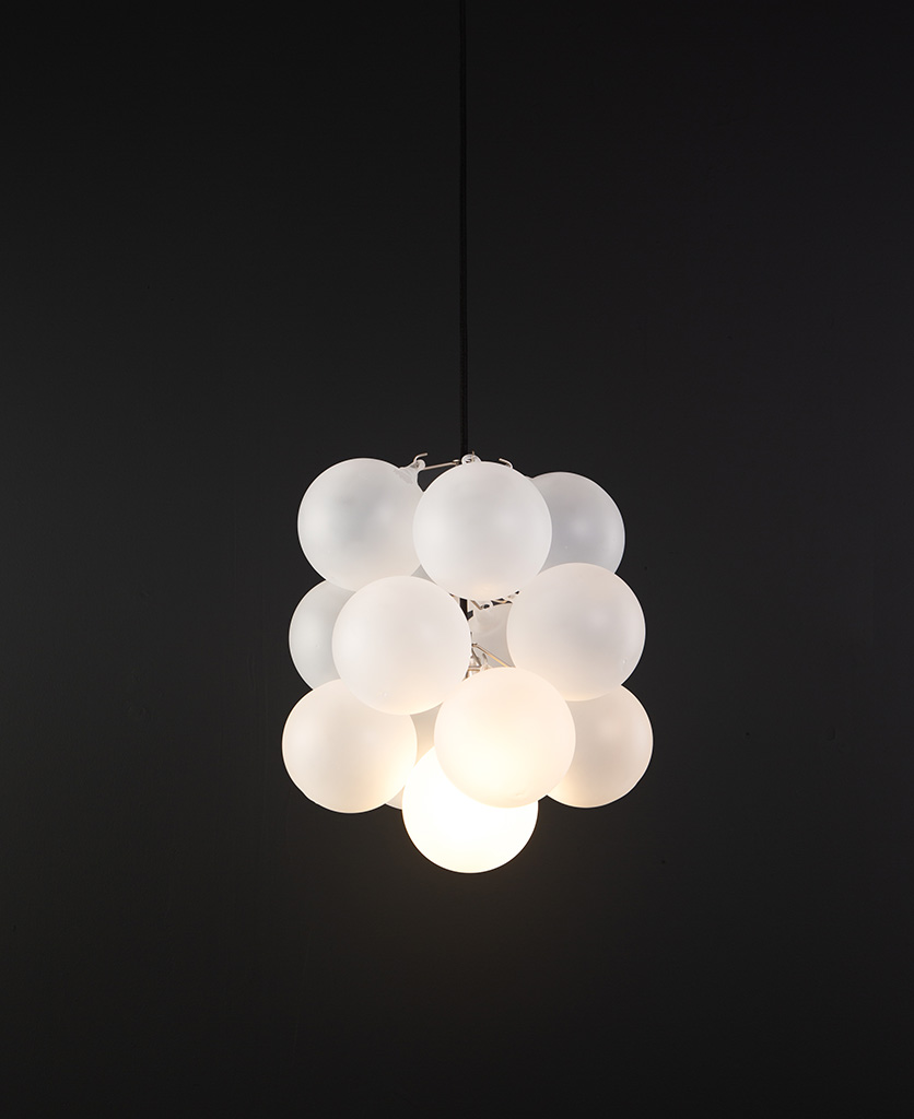 frosted glass bubble chandelier with 16 glass orbs and 1 silver bulb holder suspended from black cable against a black wall