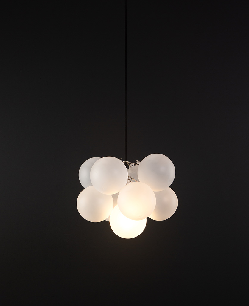 frosted glass bubble chandelier with 8 glass orbs and 1 silver bulb holder suspended from black cable against a black wall