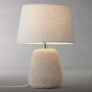 stone coloured table lamp with textured base against grey background