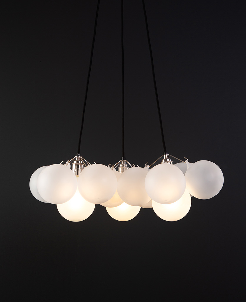 frosted bubble chandelier pendant light featuring 12 frosted baubles and silver bulb holders suspended from black fabric cable against a black wall