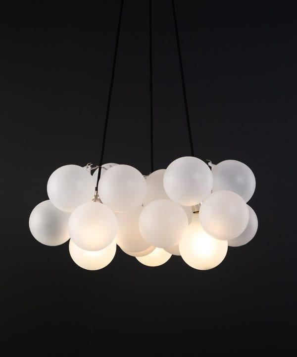 frosted bubble chandelier pendant light featuring 24 frosted baubles & 5 silver bulbholders suspended from black fabric cable against a black wall