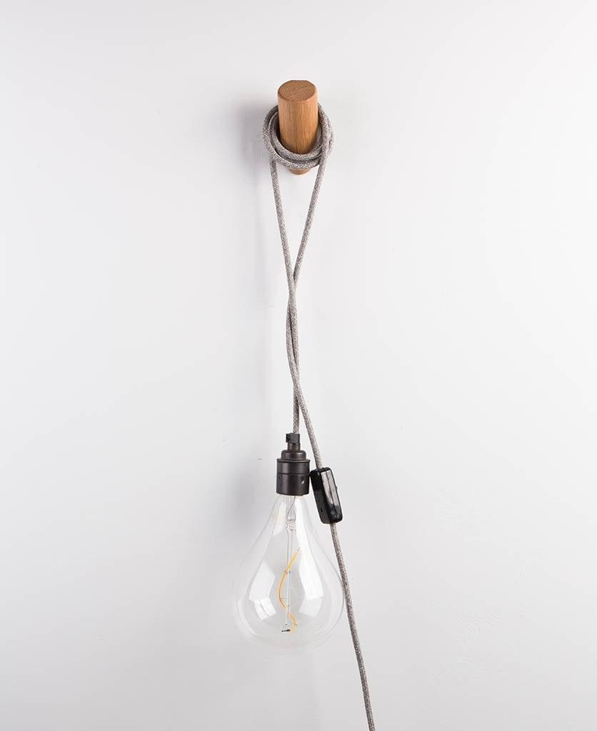 peg wall light draped around wooden peg on white wall