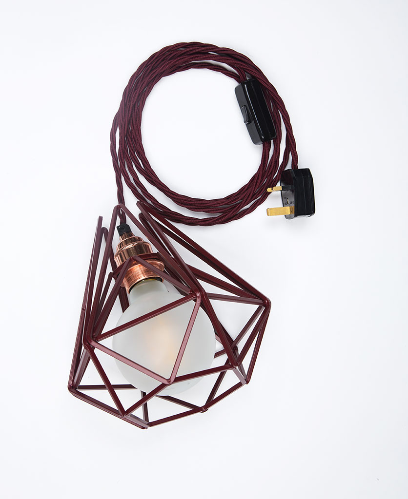 Burgundy cage shade table lamp on white background with frosted bulb, burgundy twisted cable, and polished copper bulb holder