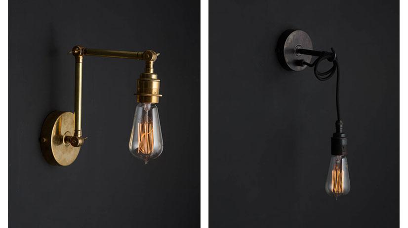 fender brass wall light and angler black wall light against black background