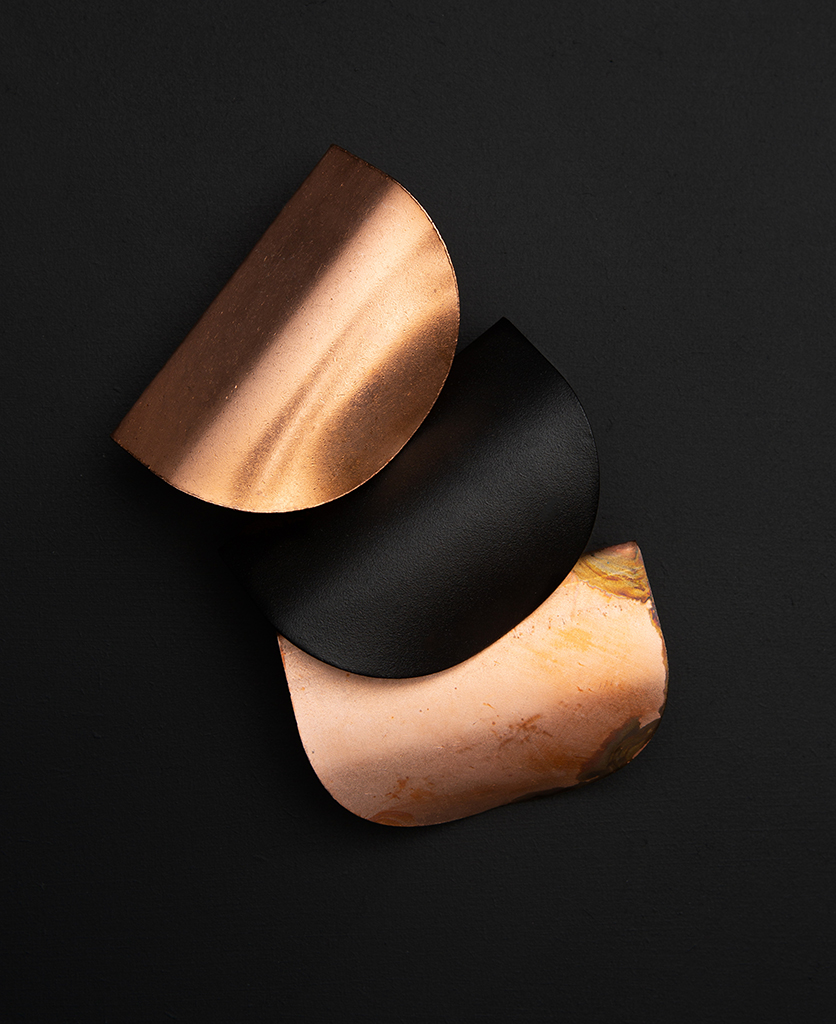 onda door pull handle group of three handles in black, copper and tarnished copper against black background