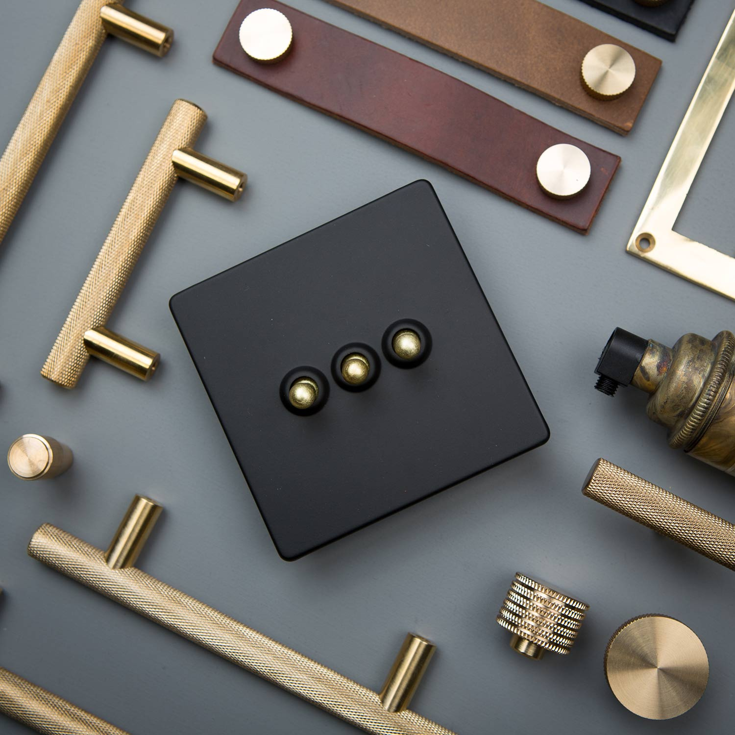 flat lay of gold and black triple dimmer, skyscraper handles, thor leather handles and various kitchen drawer handles
