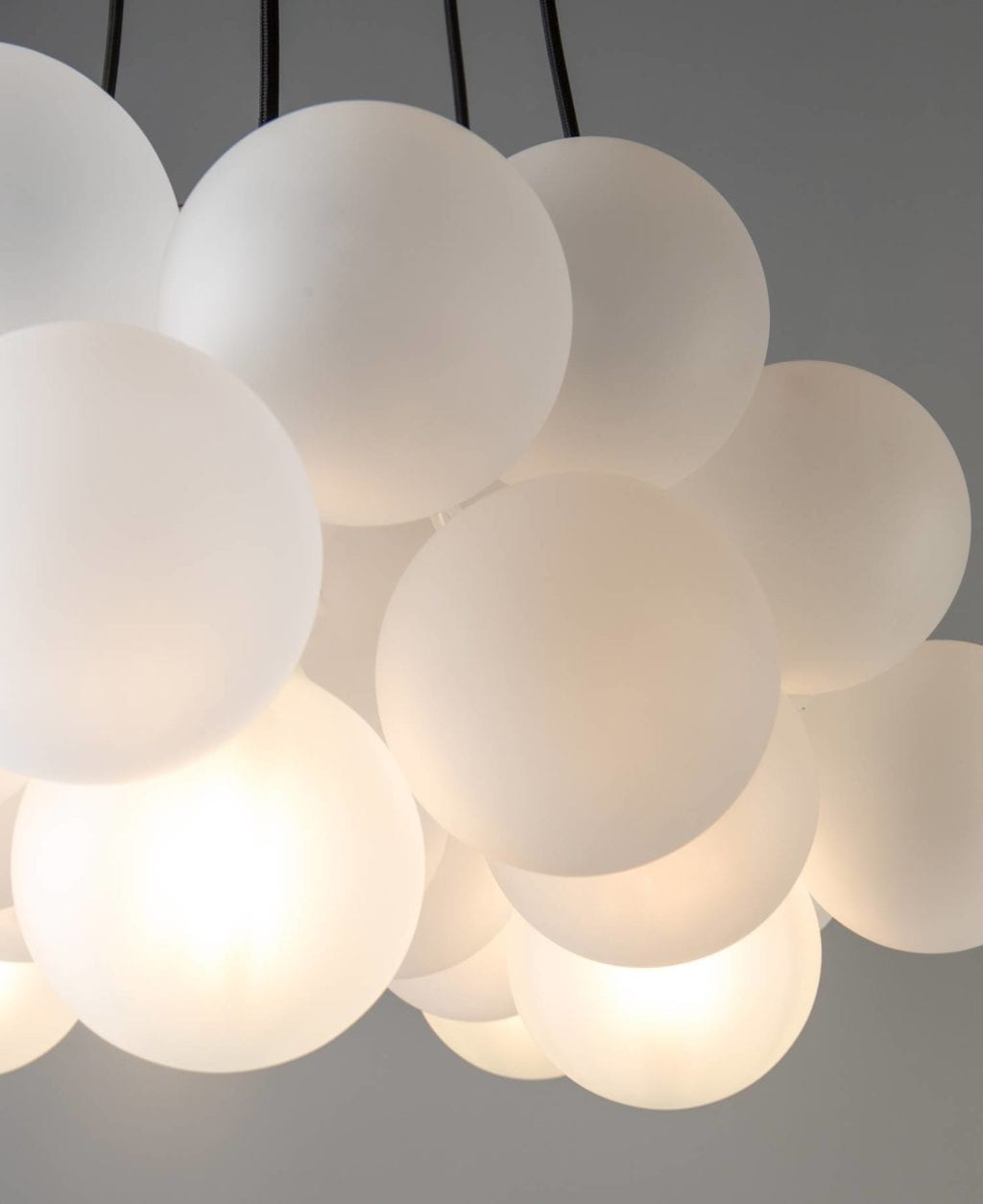 frosted bubble chandelier suspended from black fabric cable against grey background