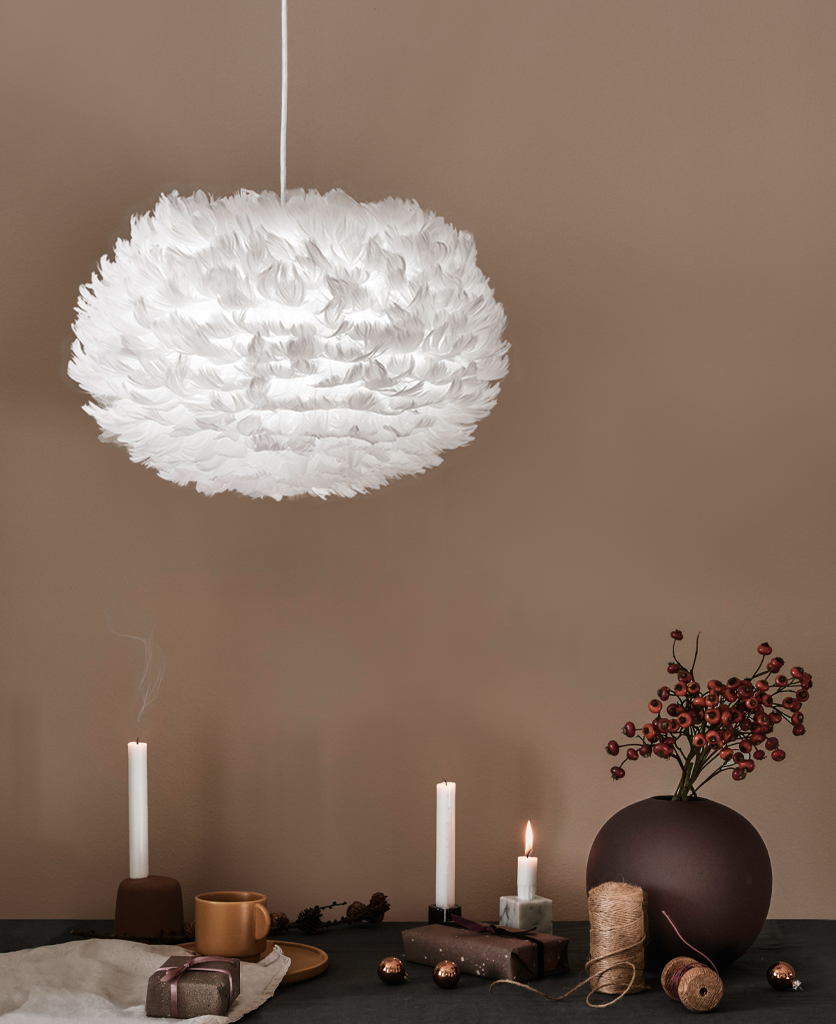 white feather pendant light suspended above a table against a light brown wall