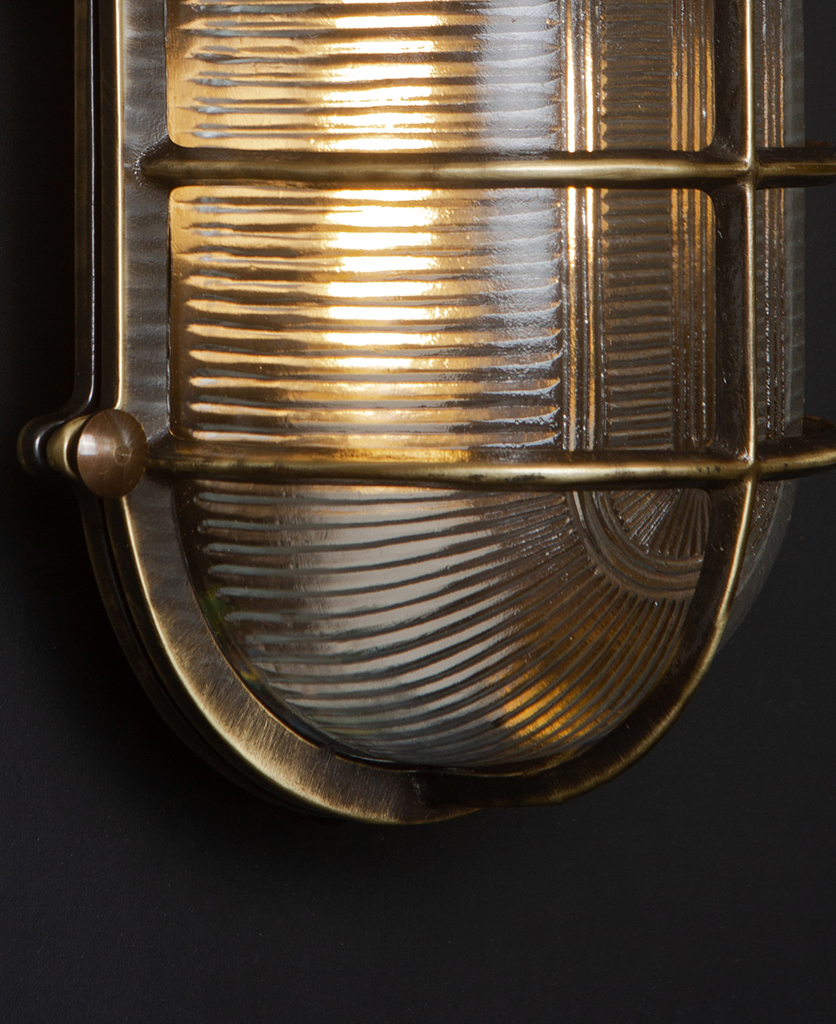 close up of aged brass lit big steve bulkhead on black wall