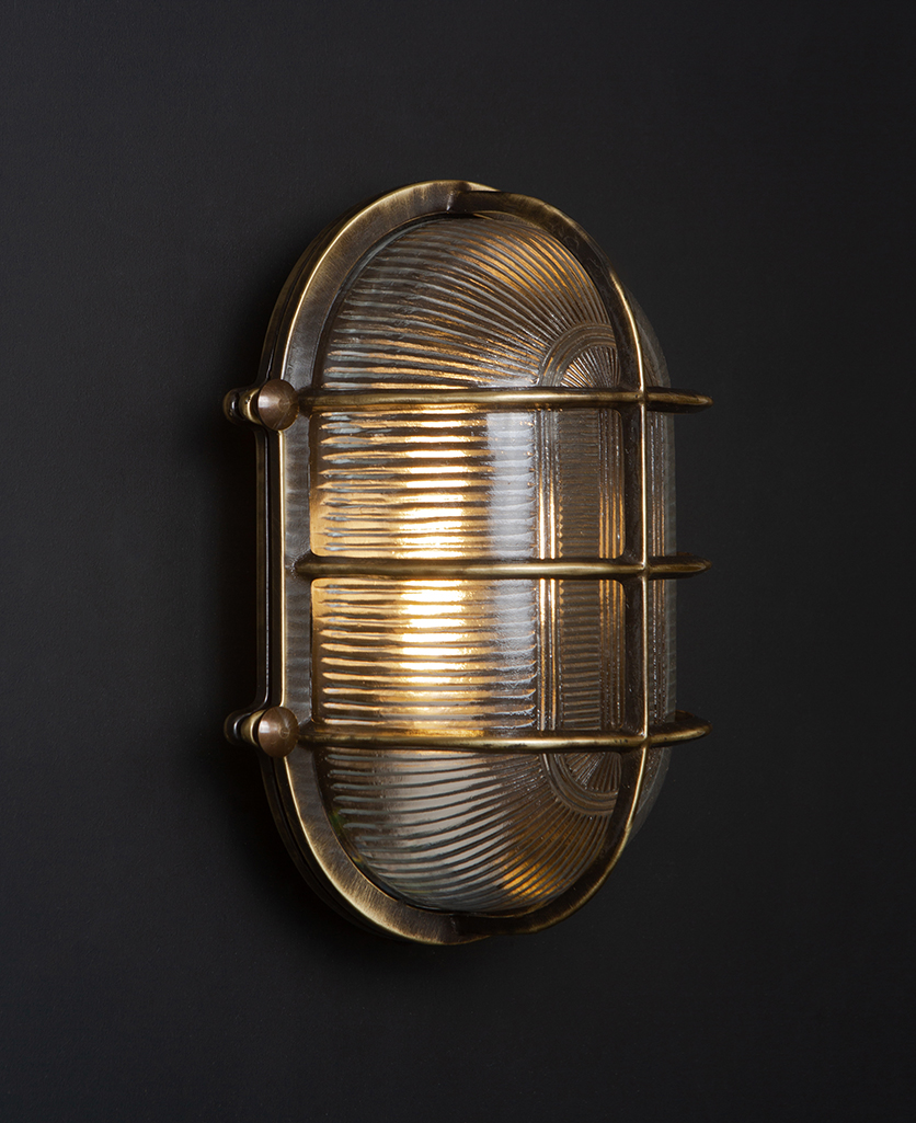 lit aged brass big steve bulkhead light on black wall