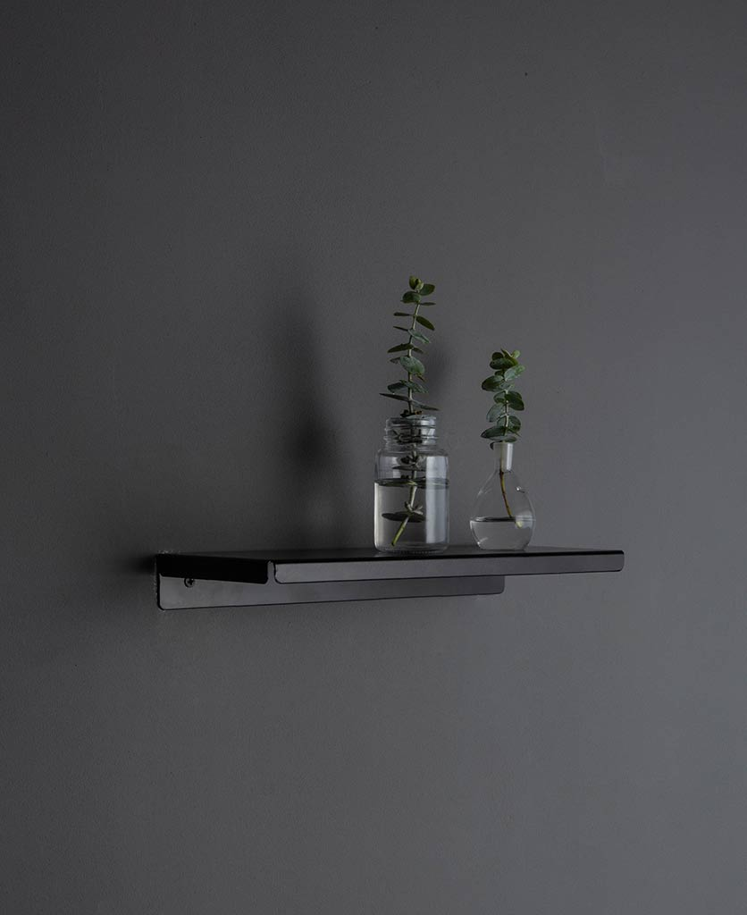 assam metal shelf with foliage in vase against grey wall
