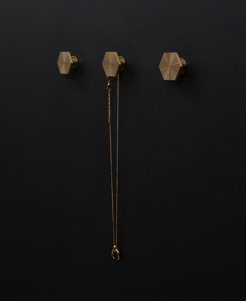 series of three bauhaus hexagonal modern coat hooks secured to a black wall