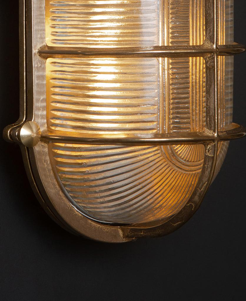 close up of lit big steve brass bulkhead wall light against black wall