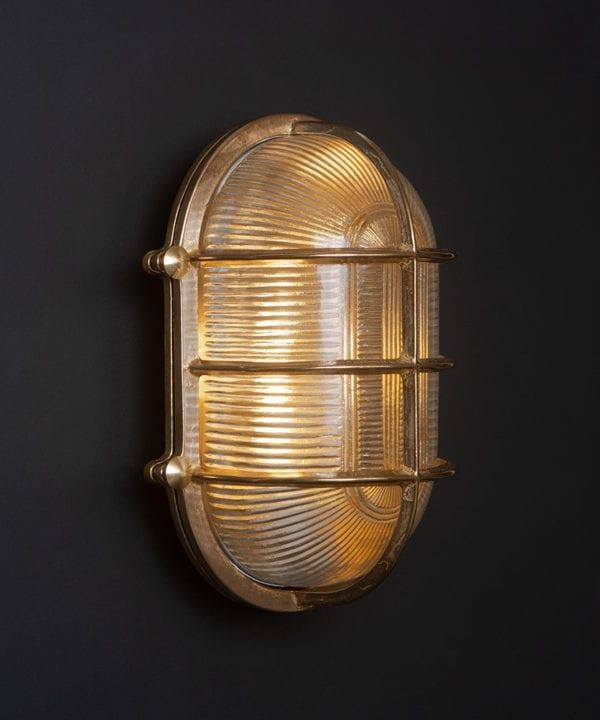 lit big steve brass bulkhead wall light against black wall