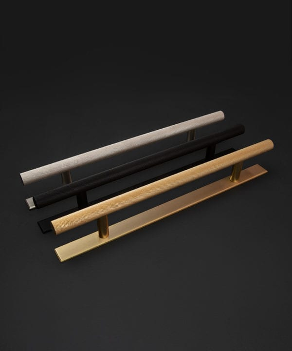 chunky skyscraper kitchen door handles with plate in silver, black and brass against black background