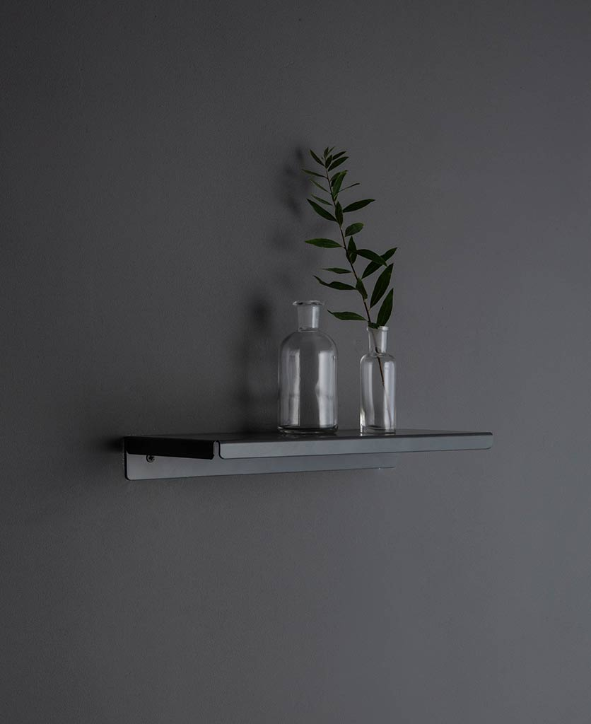 earl grey metal wall shelf with glass vases and foliage against grey background
