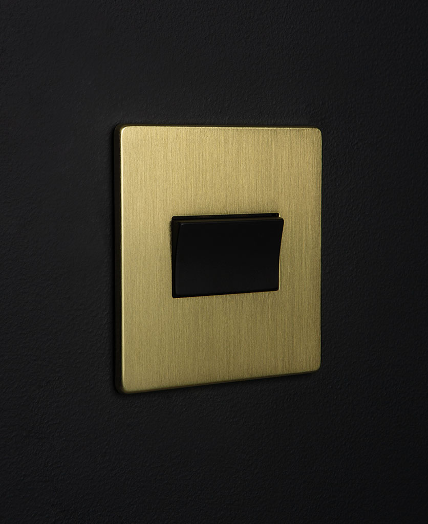 gold and black fan switch against black background