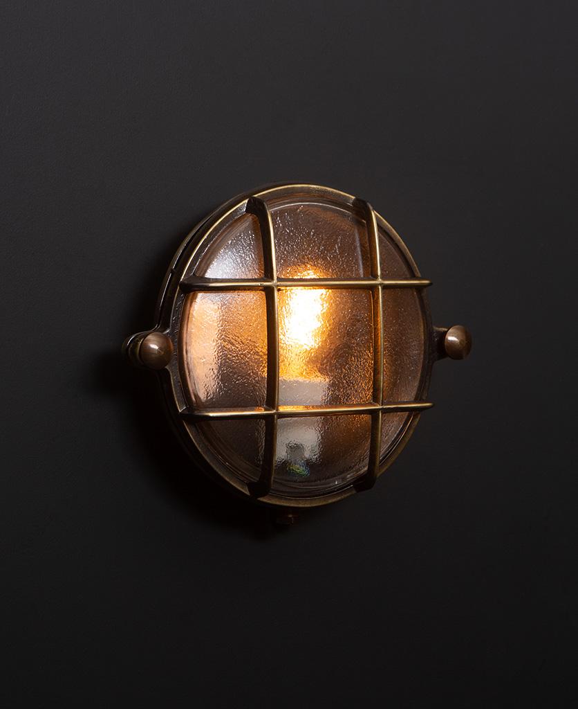 mark aged brass bulkhead light with lit bulb on black wall
