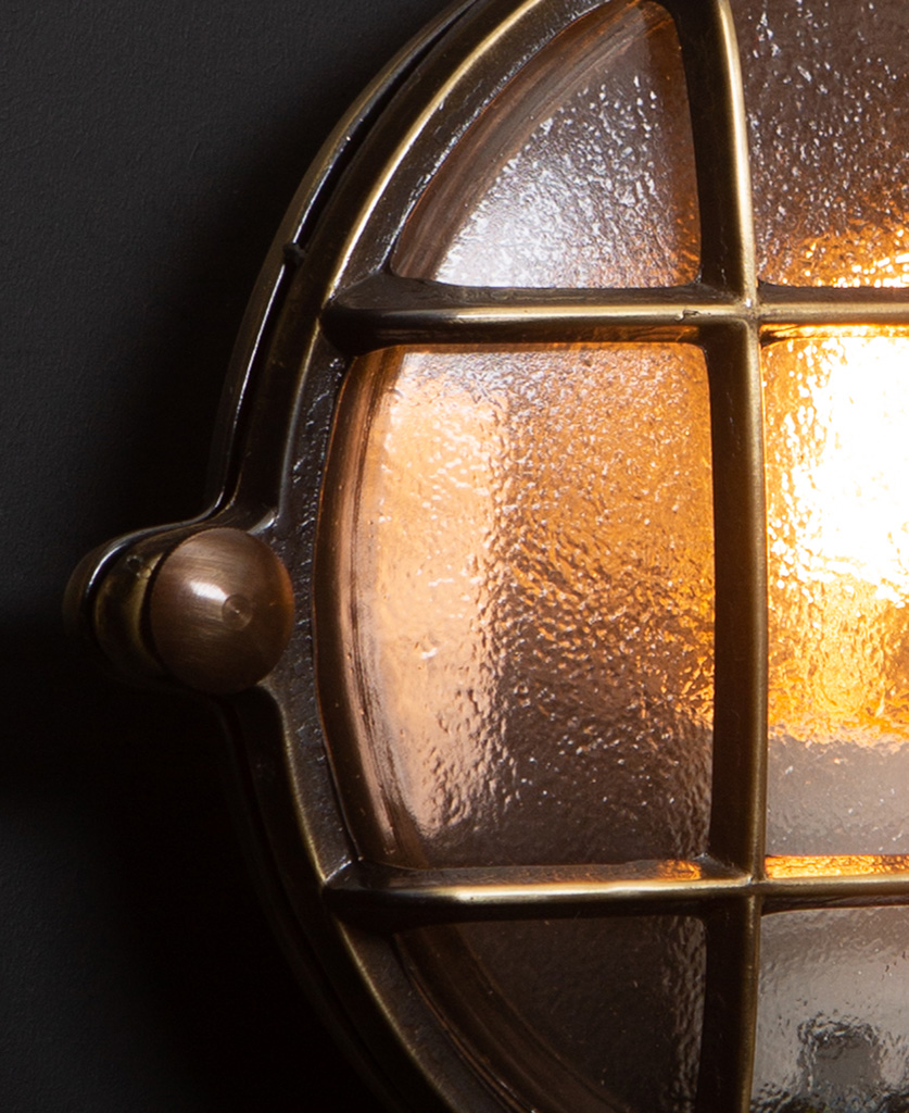 mark aged brass bulkhead light close up against black background