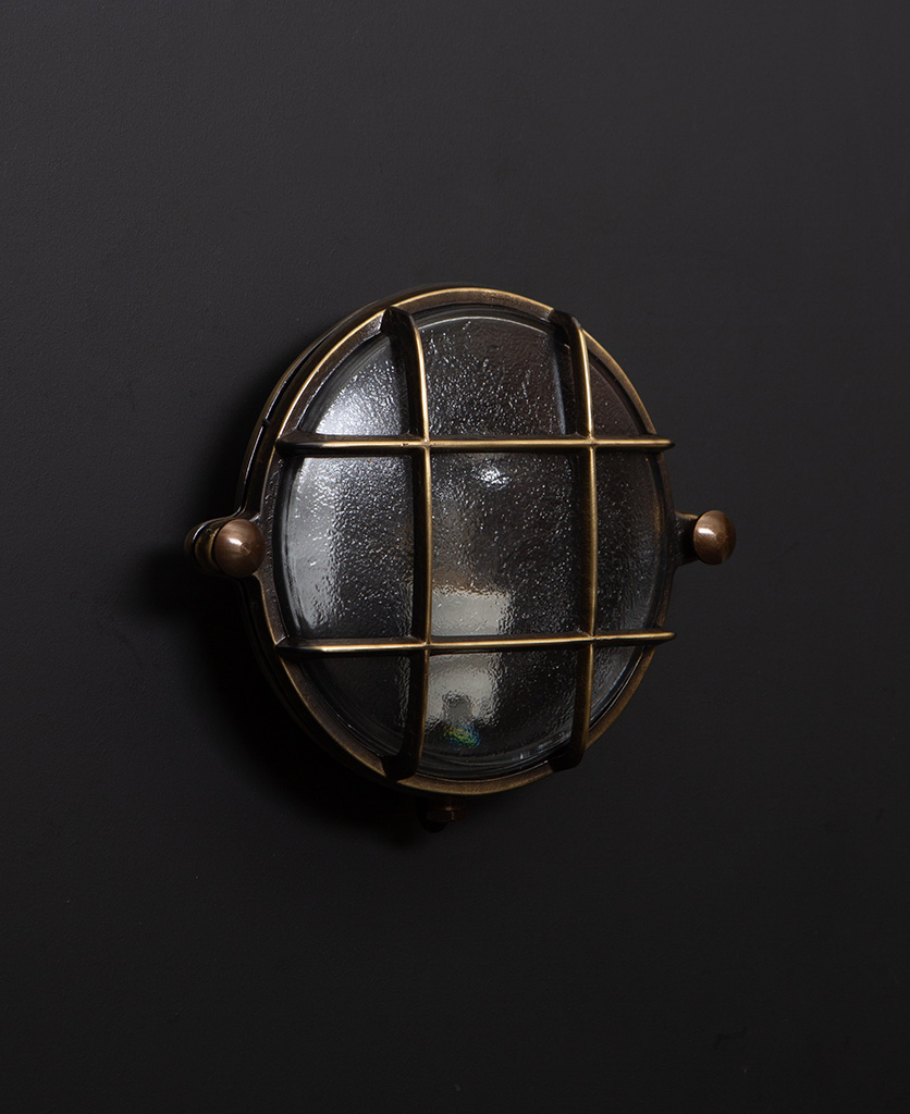 mark aged brass bulkhead light with unlit bulb on black wall