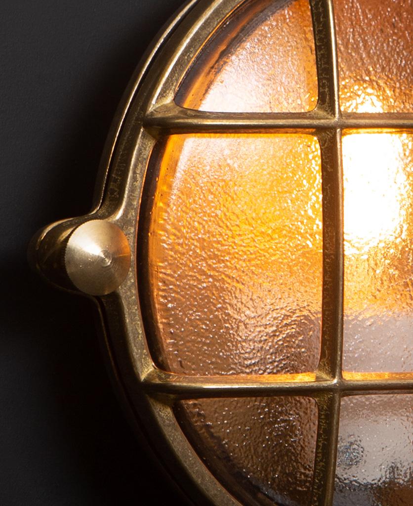 mark brass bulkhead light close up against black wall