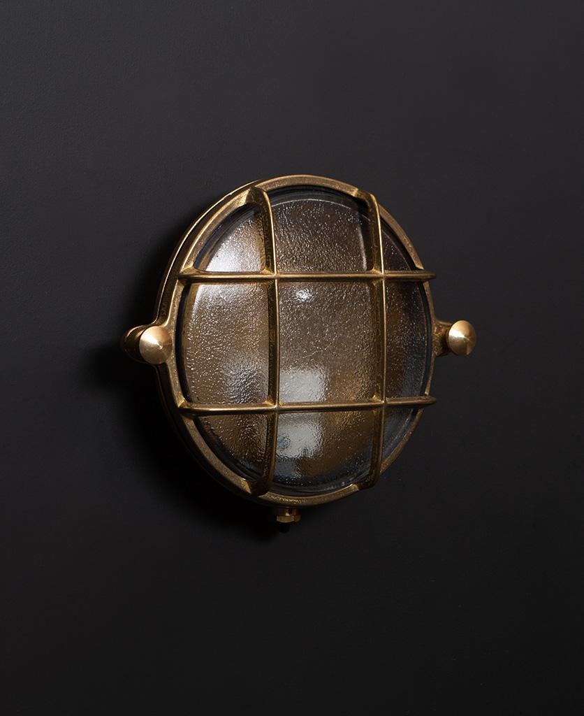 mark brass bulkhead light with unlit bulb against black wall