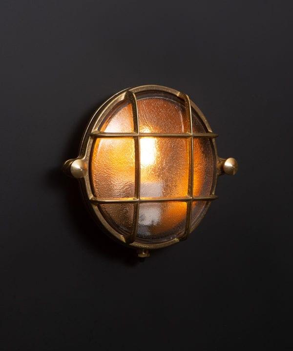 mark brass bulkhead light with lit bulb on black wall