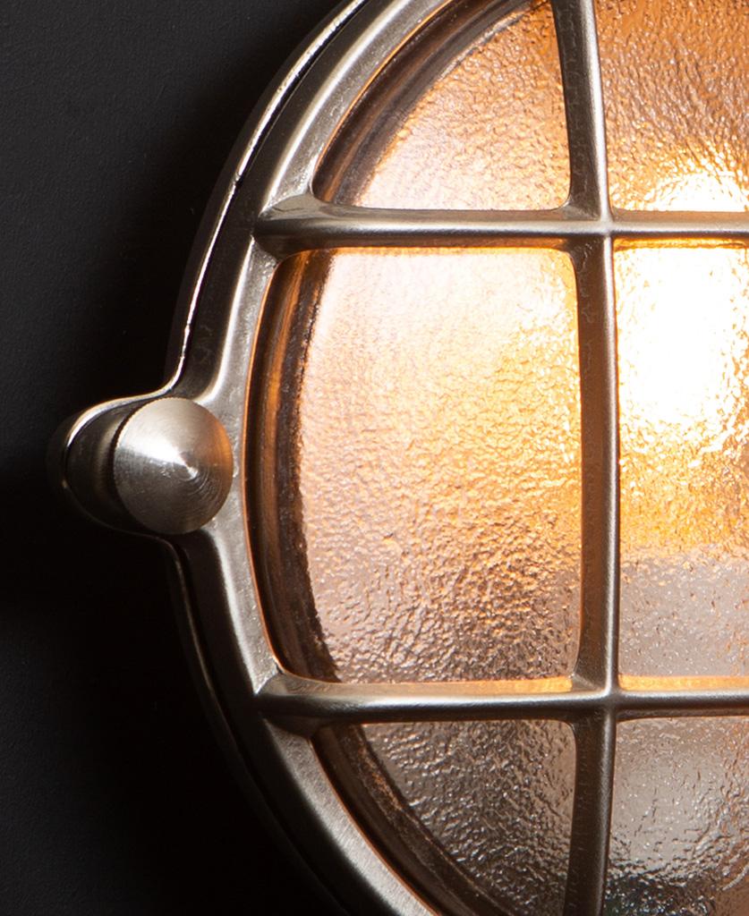 Mark silver bulkhead light close up against black wall