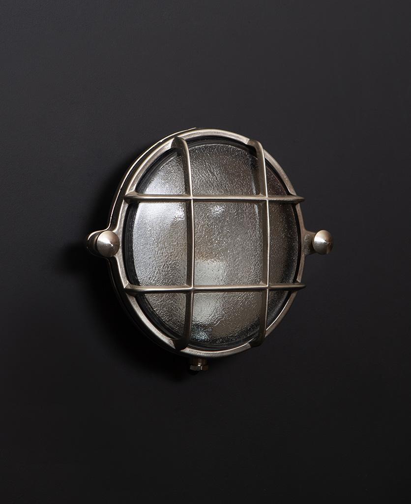 Mark silver bulkhead light with unlit bulb on black wall