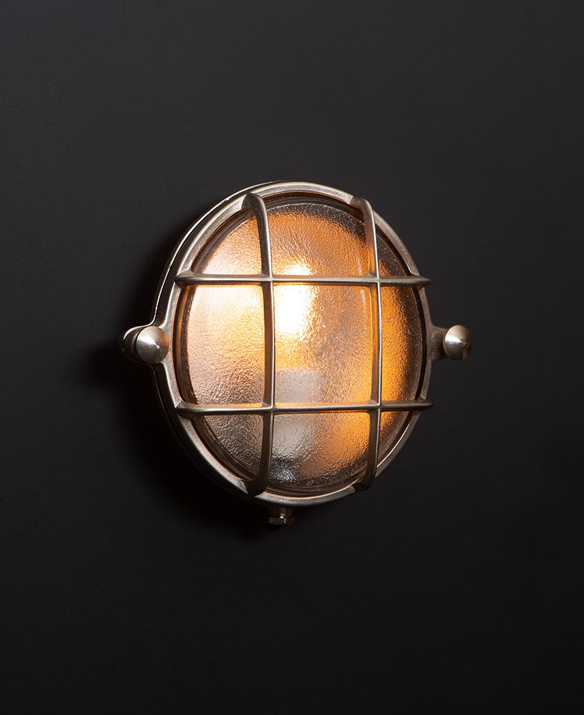 Mark silver bulkhead light with lit bulb on black wall