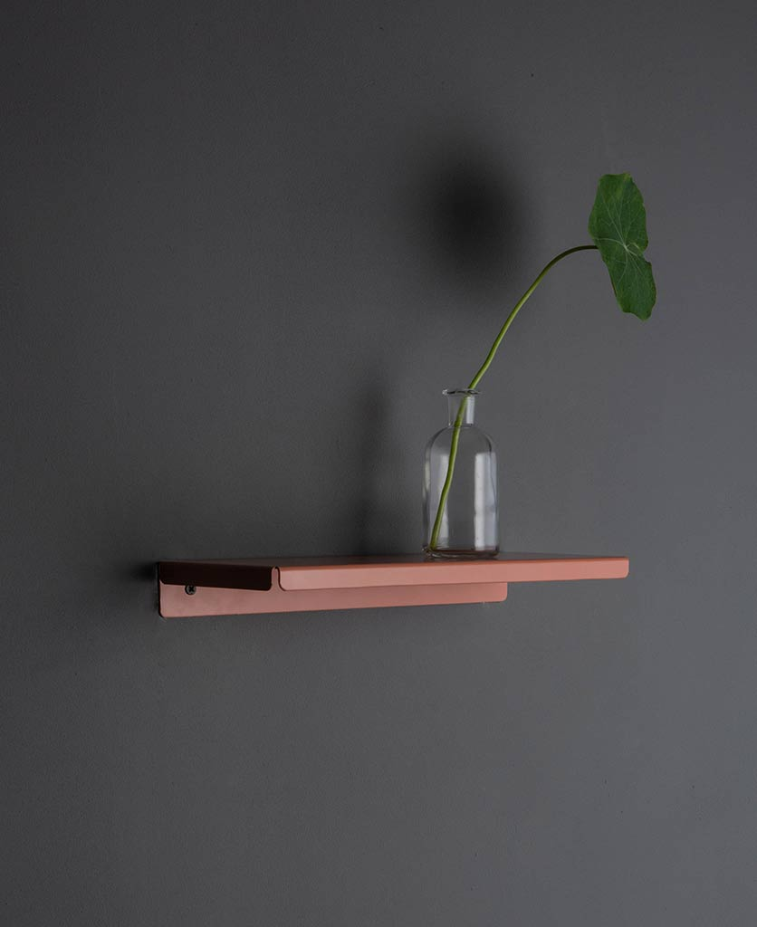 pink chai metal wall shelf with vase and foliage on grey wall