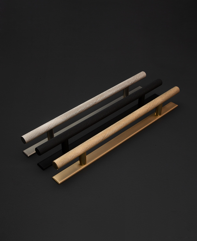 skyscraper kitchen door handles with plate in silver, black and brass against black background